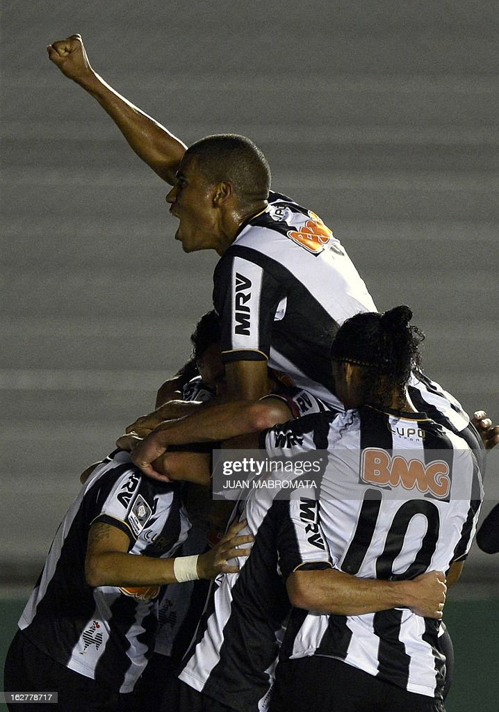 Brazilian Atletico Mineiro's forward Diego Tardelli (hidden) celebrates with teammates after scoring a goal against Argentina's Arsenal FC during their Copa Libertadores 2013 group 3 football match at Arsenal stadium in Sarandi, Buenos Aires, Argentina, on February 26, 2013. AFP PHOTO / Juan Mabromata