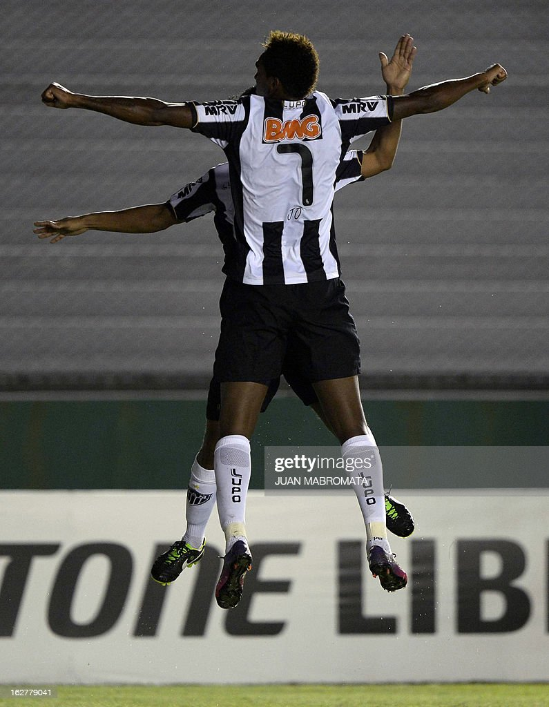 Brazilian Atletico Mineiro's forward Jo (front) celebrates with teammate midfielder Ronaldinho after scoring the team's third goal against Argentina's Arsenal FC during their Copa Libertadores 2013 group 3 football match at Arsenal stadium in Sarandi, Buenos Aires, Argentina, on February 26, 2013. AFP PHOTO / Juan Mabromata