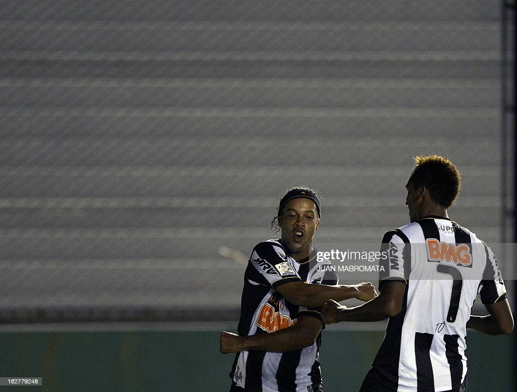 Brazilian Atletico Mineiro's forward Jo (R) celebrates with teammate midfielder Ronaldinho after scoring the team's third goal against Argentina's Arsenal FC during their Copa Libertadores 2013 group 3 football match at Arsenal stadium in Sarandi, Buenos Aires, Argentina, on February 26, 2013. AFP PHOTO / Juan Mabromata