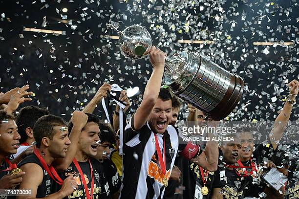 Brazilian Atletico Mineiro's players hold up the Libertadores Cup after their second leg final football match against Paraguayan Olimpia the Mineirao...