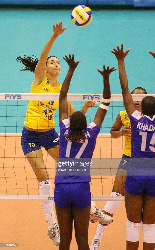 Brazilian attacker Sheilla Castro spikes the ball over Kenyan blockers Enda Rotich and Brackcides Khadambi during a match of the women's World Cup...