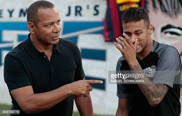 Brazilian Barcelona player Neymar gestures next to his father former footballer Neymar Senior during a fiveaside football match as part of a Neymar...