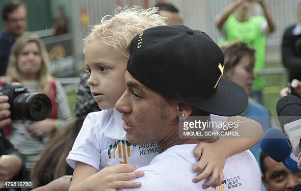 Brazilian Barcelona player Neymar holds his son Davi Lucca during an event with children with different capabilities and professional athletes taking...