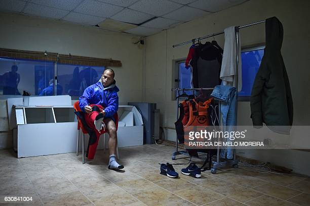 Brazilian big wave surfer Marcelo Luna puts on his wetsuit in preparation for a surf session off Prada do Norte in Nazare on November 19 2016 Saved...