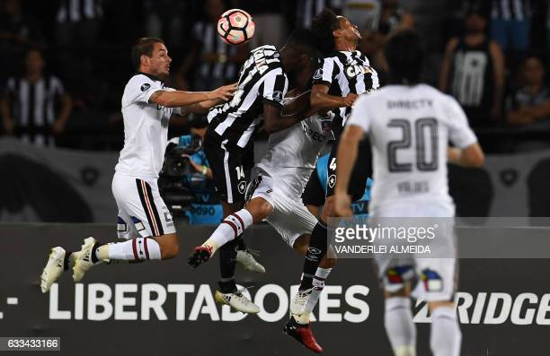 Brazilian Botafogo players Marcelo Conceicao and Jonas Silva vie for the ball with Chile's ColoColo player Jaime Valdes during their Copa...