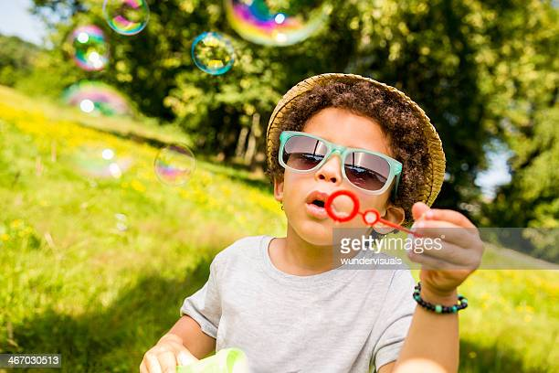 Brazilian boy busy blowing bubbles in nature