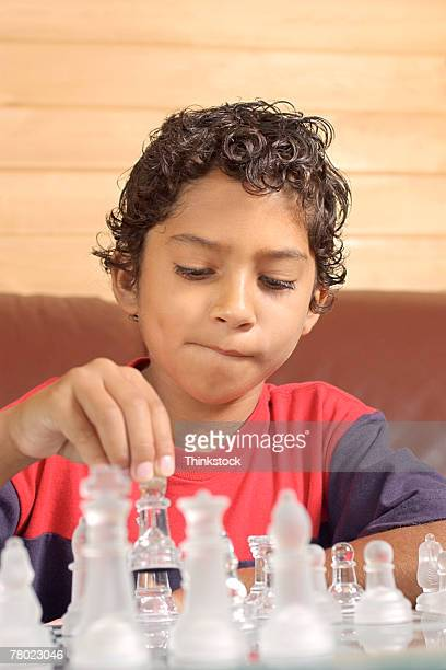 Brazilian boy lifts a playing piece while making a strategic move in chess.