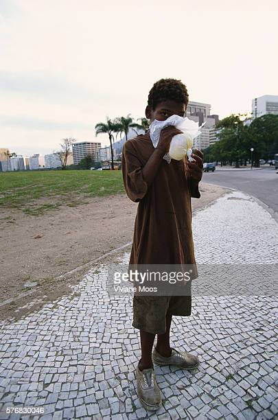 A Brazilian boy one of thousands of the country's homeless children sniffs glue from a bag in Rio de Janeiro