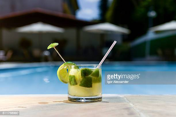 Brazilian Caipirinha cachaça at the edge of a swimming in a summer sunny day
