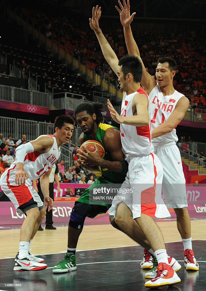 Brazilian centre Nene Hilario (C) vies with Chinese guard Guo Ailun (L) and Chinese centre Yi Jianlian (R) during the men's preliminary round group A basketball match China vs Brazil of the London 2012 Olympic Games on August 4, 2012 at the basketball arena in London.