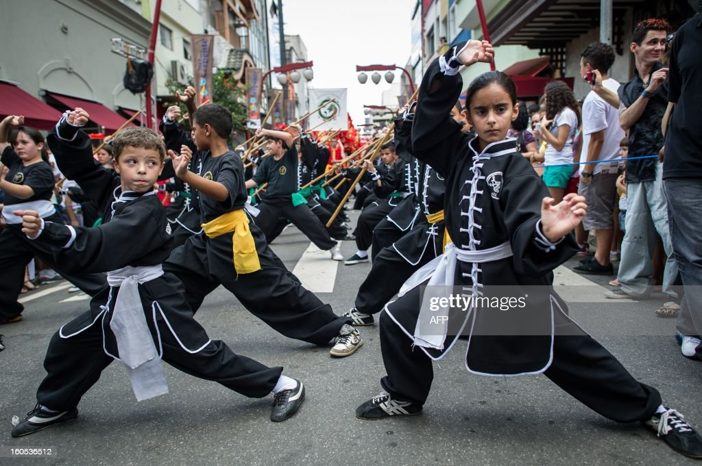 Brazilian children perform kungfu during the Chinese lunar new year celebrations at Liberdade district in Sao Paulo, Brazil, on February 2, 2013. The Chinese lunar New Year's day will be February 10 as the year of snake in Chinese zodiac calendar. AFP PHOTO/Yasuyoshi CHIBA