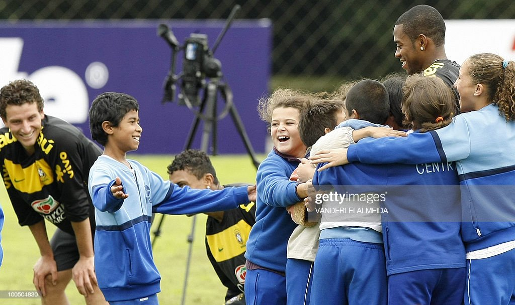 Brazilian children with special capabilities embrace Robinho (R) at the end of a traning session in Curitiba, southern Brazil on May 25, 2010.