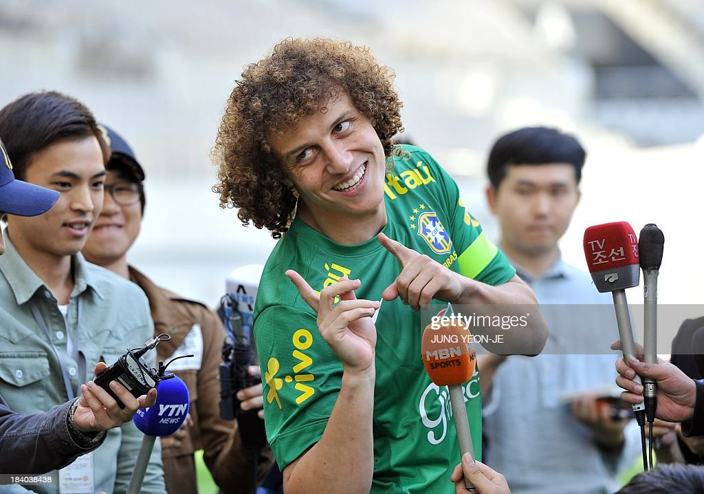 Brazilian defender David Luiz (C) gestures during an interview before a training session ahead of a friendly football match with South Korea in Seoul on October 11, 2013. The match will take place at Seoul World Cup Stadium on October 12. According to the Korea Football Association, it is expected to draw a near-sellout crowd at the 66,000-seat venue and set a new attendance record for a football friendly there. AFP PHOTO / JUNG YEON-JE