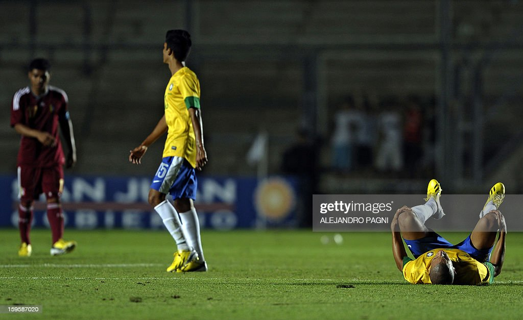 Brazilian defender Doria (R) lies on the ground at the end of their South American U-20 Championship Group B qualifier football match against Venezuela, at the Bicentenario stadium in San Juan, Argentina, on January 16, 2013. Four South American teams will qualify for the FIFA U-20 World Cup Turkey 2013. AFP PHOTO / ALEJANDRO PAGNI