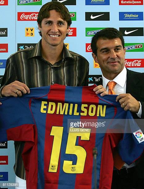 Brazilian defender Jose Gomes Edmilson Moraes shows his new Barcelona FC club jersey next to Barcelona's club president Joan Laporta during his...