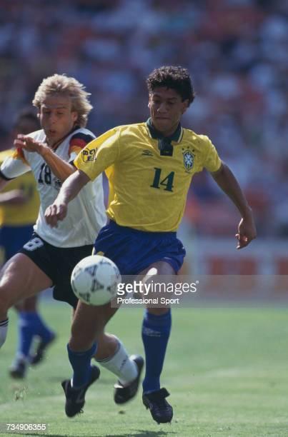 Brazilian defender Marcio Santos makes a run with the ball as German striker Jurgen Klinsmann attempts a tackle during the 1993 US Cup soccer...