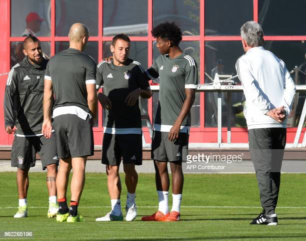 Brazilian defender Rafinha jokes with teammates Chilian midfielder Arturo Vidal and Austrian defender David Alaba as headcoach Jupp Heynckes looks on...