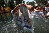 Brazilian Evangelist Christian who wears a Tallit or Jewish prayer shawl emerges from the water as he is baptised in the Jordan River on October 4...