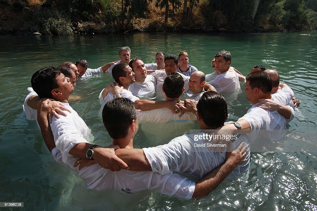 Brazilian Evangelist Christians embrace in prayer during their mass baptism ceremony in the Jordan River on October 4, 2009 at Yardenit in northern Israel. Hundreds of worshippers from northern Brazil immersed themselves in the biblical river as part of their pilgrimage to the Holy Land.
