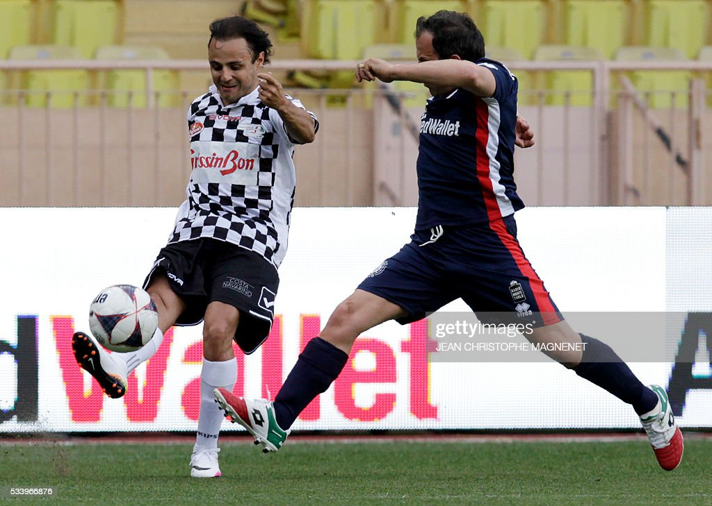 Brazilian F1 driver Felipe Massa (L) shots the ball during a charity football match between Prince Albert's Star Team and the F1 'Nazionale Piloti' drivers' team, for the benefit of the 'Association Mondiale des Amis de l'Enfance' (Protection of Children Association) on May 24, 2016 at the Louis II Stadium, in Monaco. / AFP / JEAN