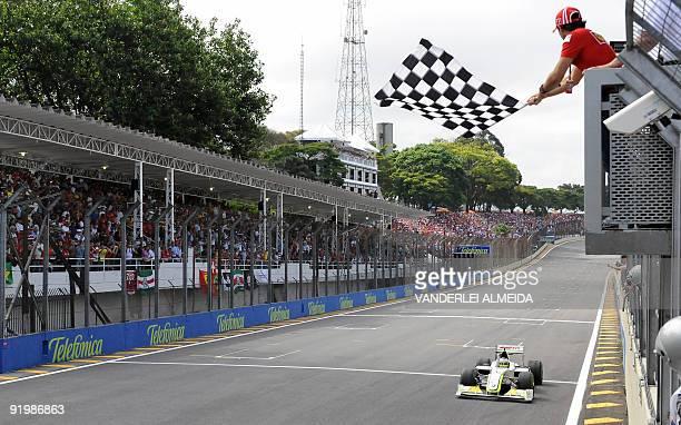 Brazilian F1 driver Felipe Massa waves the checkered flag to British Jenson Button of Brawn/GP at the end of the Brazilian F1 Gran Prix at the...