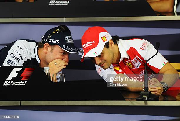 Brazilian F1 drivers Rubens Barrichello of Williams and Felipe Massa of Ferrari talk as they attend the drivers press conference during previews to...