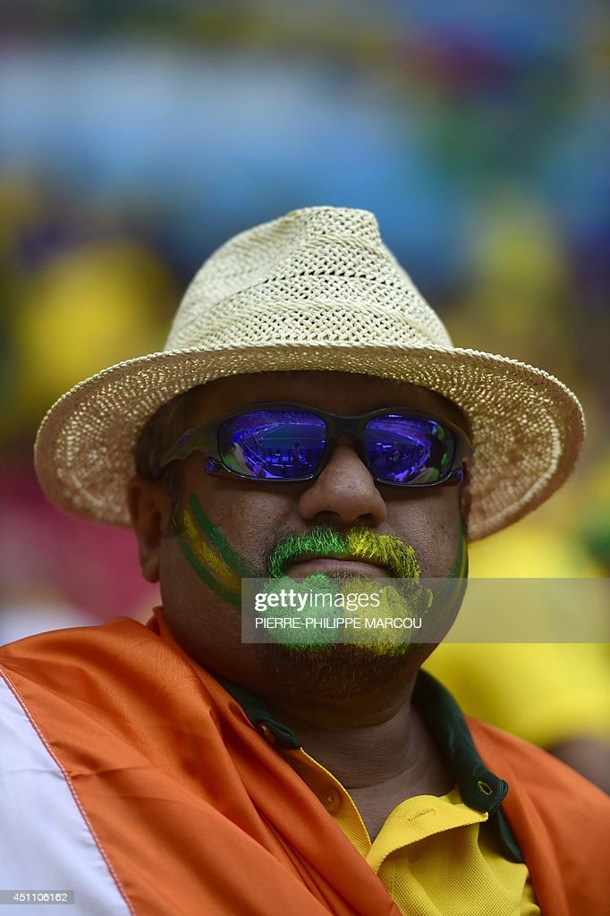 A Brazilian fan draped in an Indian tricolour looks on ahead of the Group A football match between Cameroon and Brazil at the Mane Garrincha National Stadium in Brasilia on June 23, 2014, during the 2014 FIFA World Cup.