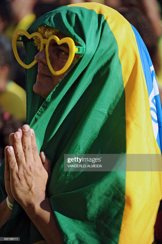A Brazilian fan prays as he watches the FIFA World Cup South Africa 2010 football match between Brazil and North Korea on a giant screen in Copacabana beach, in Rio de Janeiro, Brazil on June 15, 2010.