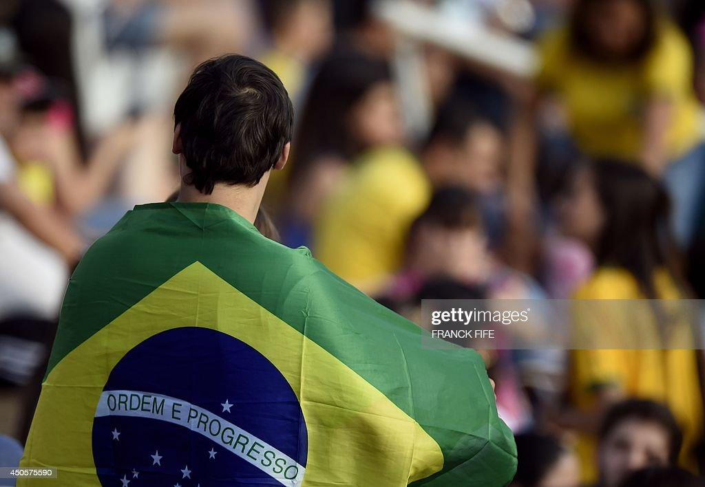 A Brazilian fan with his national flag draped around his shoulders watches France's national team take part in a training session at the Santa Cruz Stadium in Ribeirao Preto on June 13, 2014, during the 2014 FIFA World Cup in Brazil.