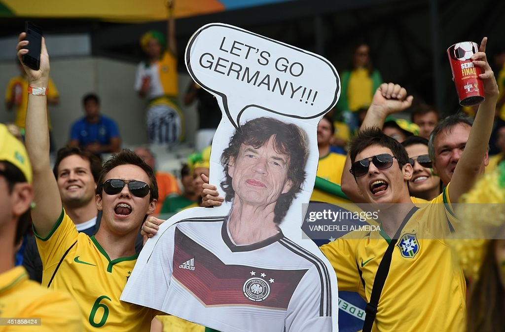 Brazilian fans hold a cardboard cutout of The Rolling Stones' Mick Jagger before the semi-final football match between Brazil and Germany at The Mineirao Stadium in Belo Horizonte during the 2014 FIFA World Cup on July 8, 2014.