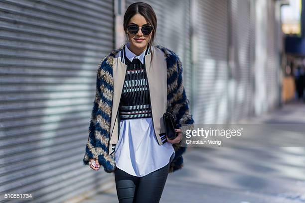 Brazilian fashion blogger Camila Coelho is wearing a jacket from Zadig and Voltaire a Public School sweater Elena Ghisellini clutc hseen outside...