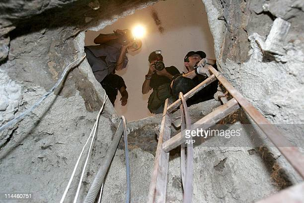 A Brazilian Federal Police agent and journalists look through the tunnel dug by the Central Bank robbers 08 August in Fortaleza northeastern Brazil...
