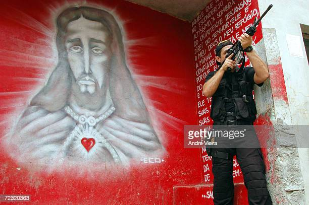 Brazilian federal police agent patrols Morro do Borel shantytown while giving security to police experts investigating the alleged execution of four...