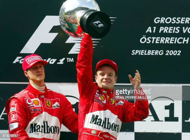Brazilian Ferrari driver Rubens Barrichello holds his trophy next to his teammate German Michael Schumacher on the podium of the Spielberg racetrack...