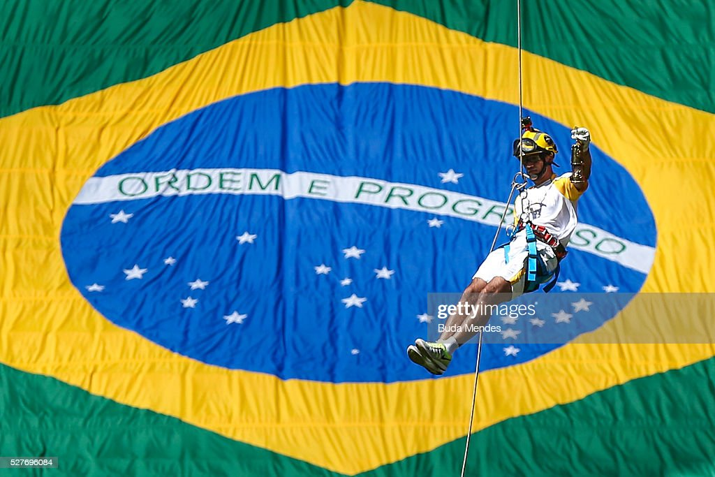 Brazilian firefighter Haudson Alves rappels with the Olympic flame as he attends the Olympic Flame torch relay at Mane Garrincha stadium on May 3, 2016 in Brasilia, Brazil. The Olympic torch will pass through 329 cities from all states from the north to the south of Brazil, until arriving in Rio de Janeiro on August 5, to lit the cauldron.