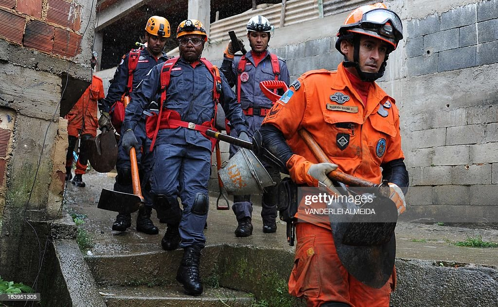 Brazilian firefighters rescue team walk upon arrival at a poor neighbourhood in Petropolis, 68 km north of Rio de Janeiro, to work on search operations following landslides caused by heavy rains hitting the area, on March 18, 2013. Floodings and mudslides triggered by heavy rains have already left 13 people dead over the past 24 hours in the Brazilian tourist town of Petropolis, whose historic center is under water.