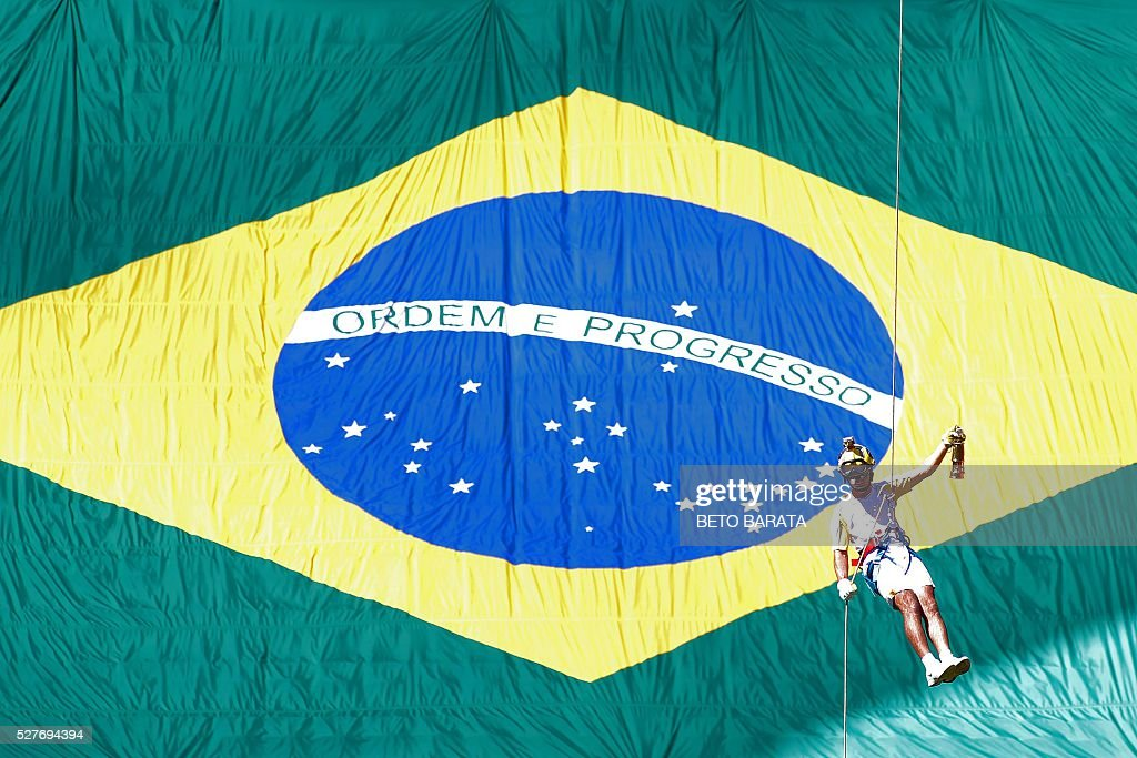 Brazilian fireman Haudson Alves descends from a helicopter carrying the Olympic flame on a lantern at the Brasilia National Stadium in Brasilia on May 3, 2016. Embattled President Dilma Rousseff greeted the Olympic flame in Brazil on Tuesday, promising not to allow a raging political crisis, which could see her suspended within days, to spoil the Rio Games. The torch will now be carried in a relay by 12,000 people through 329 cities, ending in Rio's Maracana stadium on August 5 for the opening ceremony. / AFP / BETO