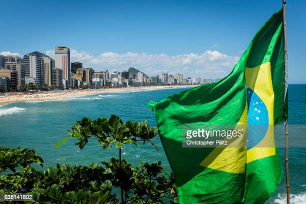 Brazilian flag flutters in wind at far end of Leblon beach.