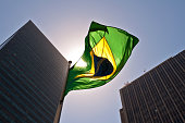 Brazilian National Flag against Skyscrapers by Sunset.