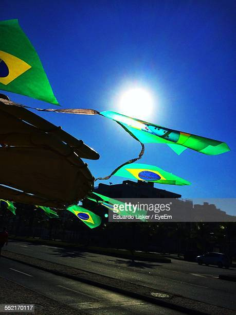Brazilian Flags Hanging Against Blue Sky