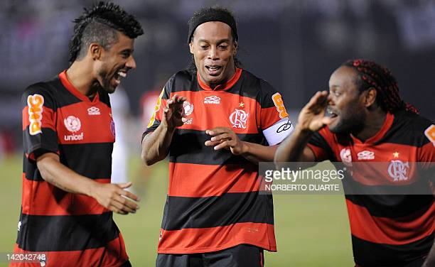 Brazilian Flamengo's Vagner Love celebrates with teammates Ronaldinho and Leo Moura after scoring a goal against Paraguay's Olimpia during a...