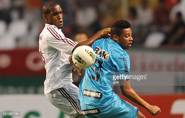 Brazilian Fluminense's Digao vies for the ball with Santos FC Andre during their Brazilian Championship football match at the Joao Havelange Olimpic...