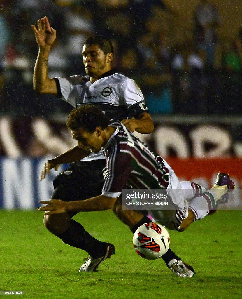 Brazilian Fluminense's Nem Wellington vies for the ball with Paraguayan Olimpia's Richard Ortiz during their Copa Libertadores football match at the...