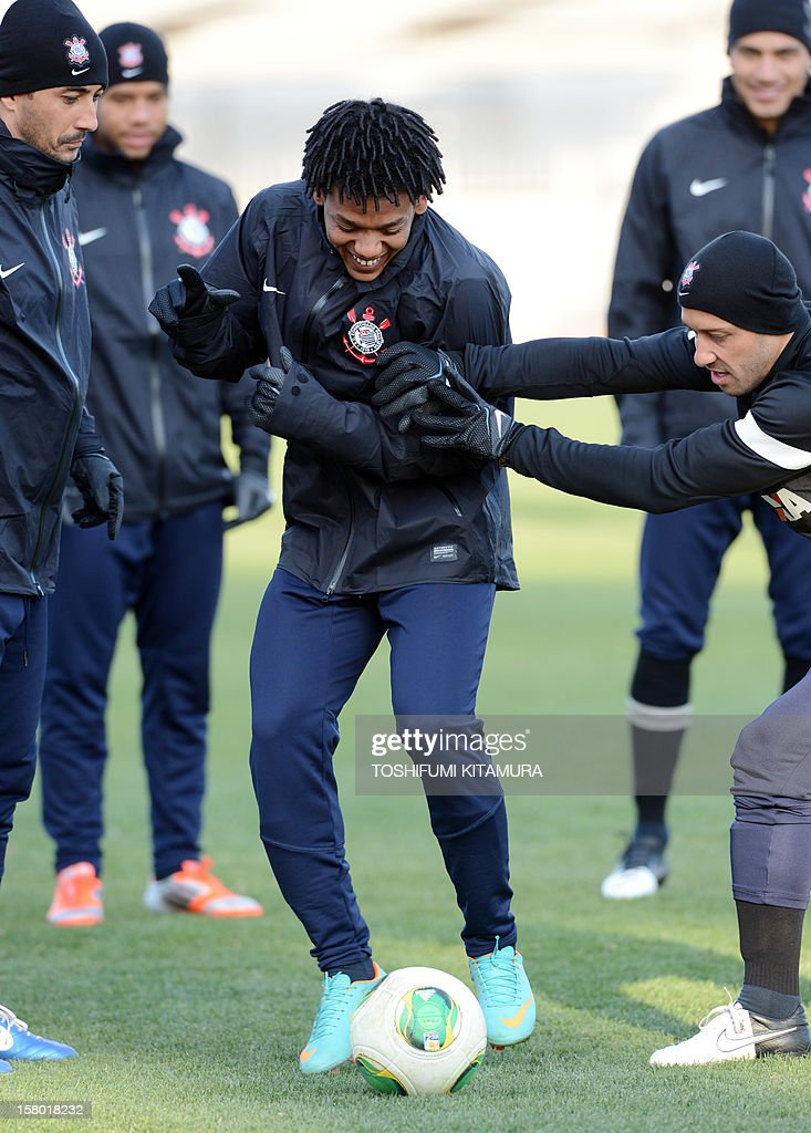 Brazilian football club team Corinthians forward Romarinho (C) is pushed by his teammate during their training session for the 2012 Club World Cup in Japan tournament at Kariya, Aichi prefecture on December 9, 2012. Corinthians will play in the semi-final match on December 12 at Toyota stadium.