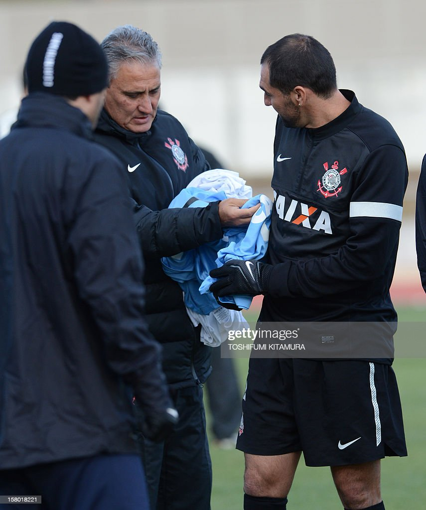 Brazilian football club team Corinthians head coach Tite (C) provides a bib to midfielder Danilo (R) during their training session for the 2012 Club World Cup in Japan tournament at Kariya, Aichi prefecture on December 9, 2012. Corinthians will play in the semi-final match on December 12 at Toyota stadium. AFP PHOTO / TOSHIFUMI KITAMURA