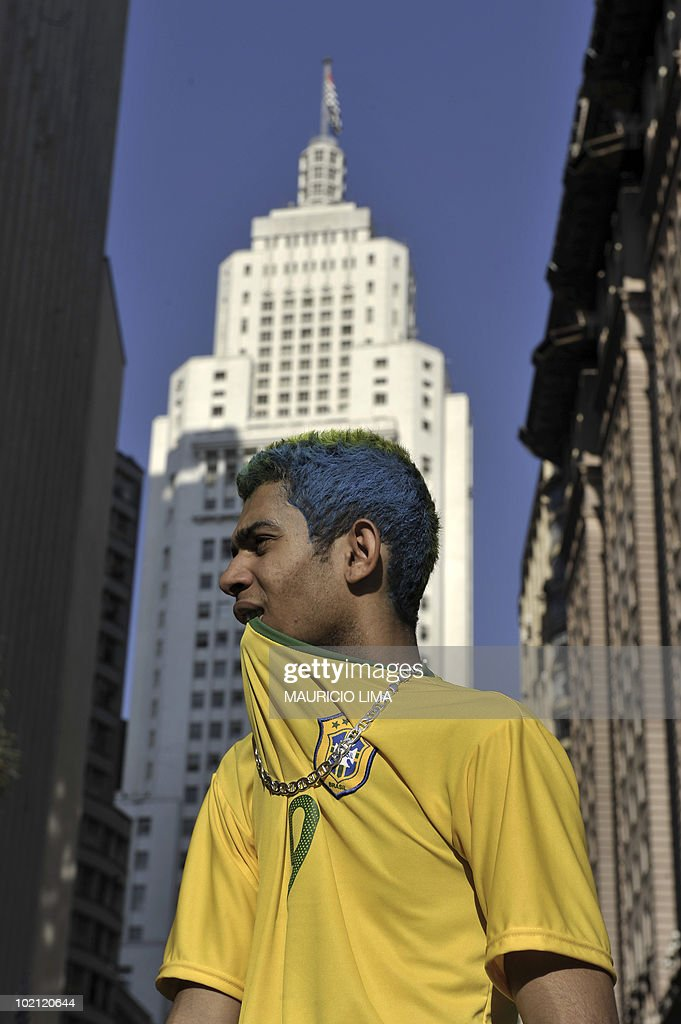 A Brazilian football fan watches the first half time of the FIFA World Cup South Africa 2010 Group G match between Brazil and North Korea outside a bar, in downtown Sao Paulo, Brazil, on June 15, 2010. Brazil won 2-1. AFP PHOTO/Mauricio LIMA