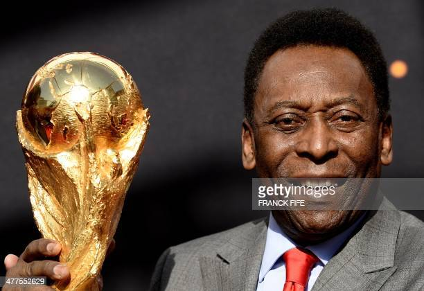 Brazilian football legend Pele poses with the FIFA World Cup trophy during a press conference on March 9 2014 outside the Hotel de Ville in Paris The...