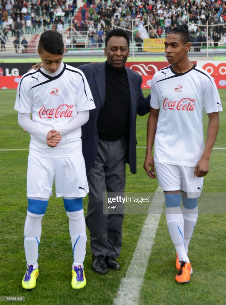 Brazilian football legend Pele poses with young football players before the start of their match as part of the Copa Cola Cola youth football tournament at the Stade Mustapha Tchaker Stadium in Blida, south of the capital Algiers, on March 5, 2014.