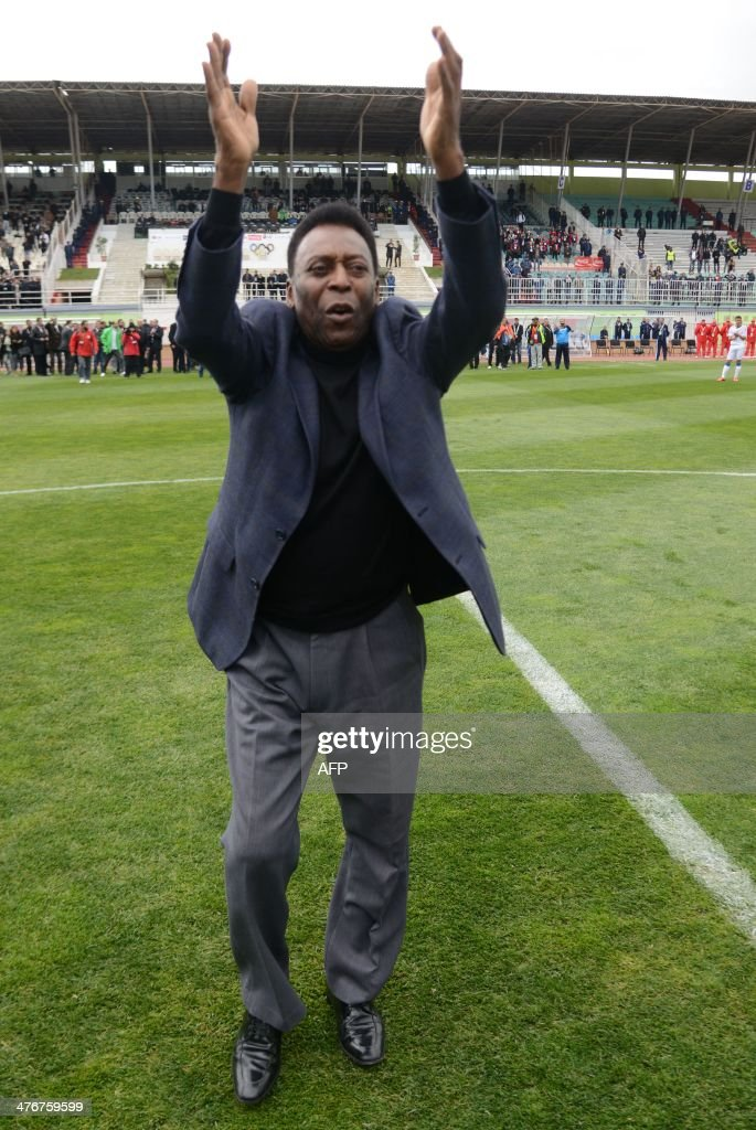 Brazilian football legend Pele waves to the crowd walking on the field before a match of the Copa Cola Cola youth football tournament at the Stade Mustapha Tchaker Stadium in Blida, south of the capital Algiers, on March 5, 2014.
