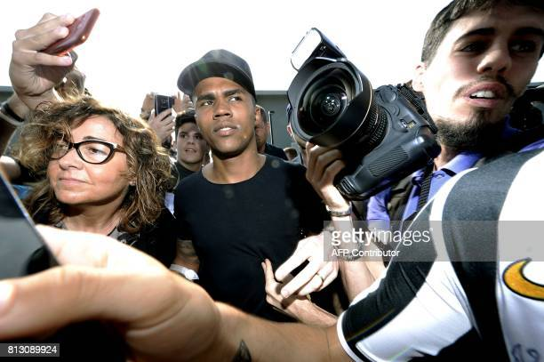 Brazilian football player Douglas Costa is surrounded by supporters and photographers upon his arrival at the Juventus' Medical Center in Turin on...